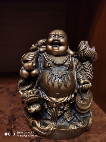 Статуэтка золотого смеющегося Будды, символизирующего достаток в доме