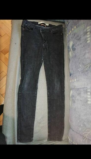 Crne farmerke, nogavice su pripijene. Velicina je L, dubok struk