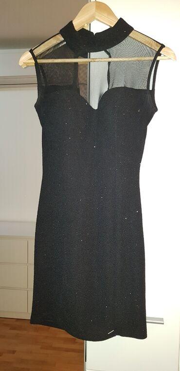 Mala crna svetlucava haljina. Veoma atraktivnog kroja. Odgovara