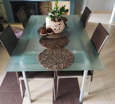 Τραπεζαρία γυάλινη με 4 καφέ σκούρο καρέκλες σε υλικό δερμάτινης