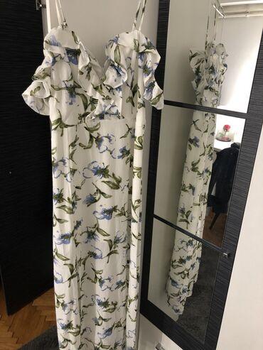 Duga haljina na bratele sa rukavima ispod ramena. Ima dva proreza sa