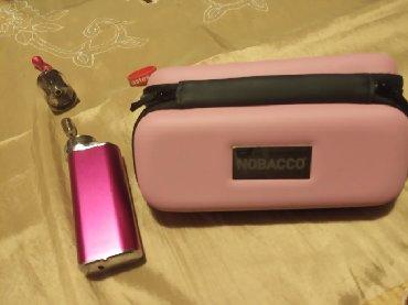 Nobacco ηλεκτρονικό τσιγάρο φούξια χρώματος με τη θήκη του.στη δεύτερη