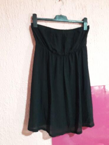 Crna haljina koja pada od grudi i tegli se. M/L velicina