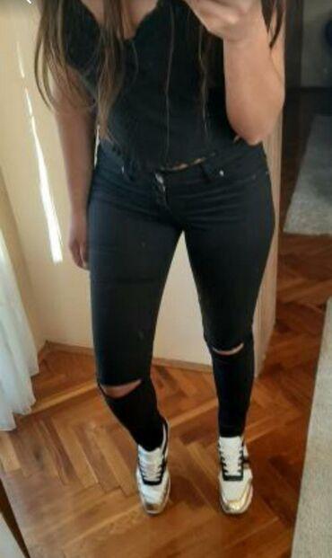 Pantalone sa na - Srbija: Uske crne pantalone sa elastinom. Cepane na kolenima sa klasičnim