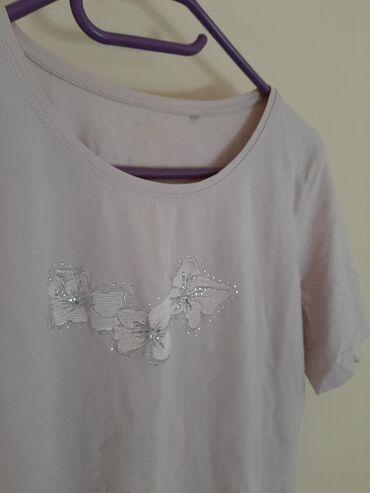 Svetlo roze majica. Veličina M/L. Sa cvetovima i sitnim cirkonima. Ima