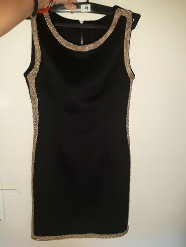 Prodajem crnu haljinu sa zlatnim detaljima, nazad se zakopčava, a