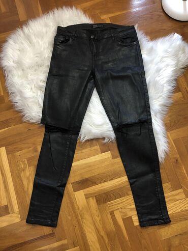 Crne zenske pantalone, sjajne. ZARA. Velicina 38. Kolena su iscepana