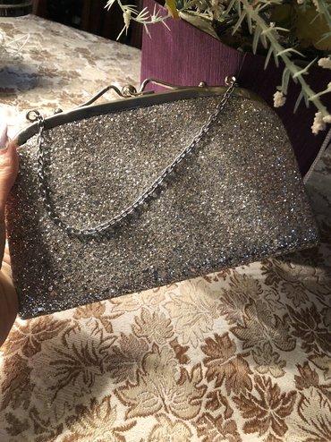 Gümüşü rengde ziyafet çantasi.Çantanin zencirden ibaret tutacaği