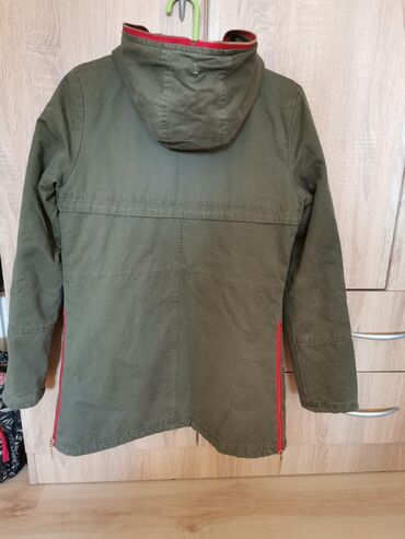 Jednom obucena maslinasto zelena jakna sa crvenim cibzarima, topla je