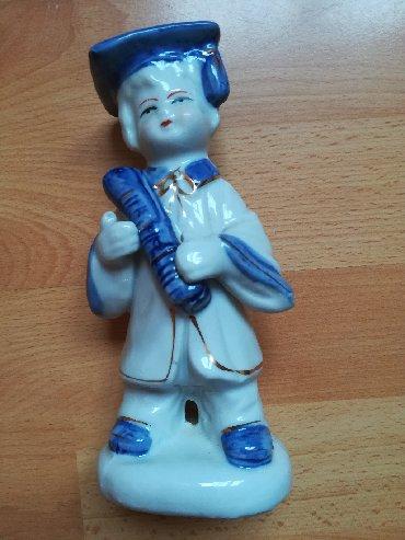 Kućni dekor - Vranje: Keramička figura dečaka školarca koji svira, visina 18 cm, kao nova