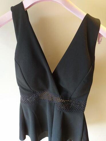 Crna majicica vezuje se oko vrata, ojacana kod grudi, gola ledja