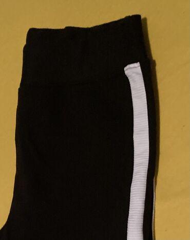 Deblje crne pantalone sa belom štraftom, u struku široka guma