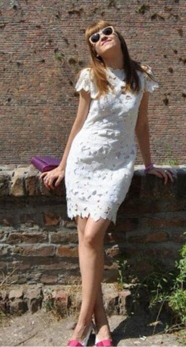 Atraktivna bela haljina od čipke sa otvorenim leđima, koja prati