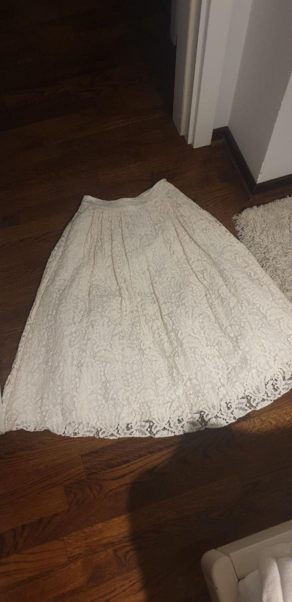 Čipkana suknja, kroj A, postavljena sa vise slojeva, i tilom, ima dzepove sa strane, dublji struk, duzina do lista