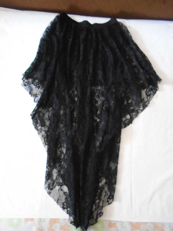 Crna suknja od til/čipke, ima suknjicu ispod, asimetričnog kroja, napred i pozadi na V , nošena jednom ili nijednom