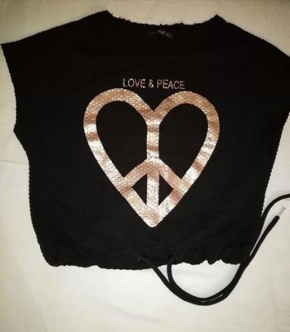 Crna crop top majica, reljafastog materija sa zlatnim natpisom, ima pertle za vezivanje da bude uzi u struku, velicina pise S ali je veci i siri model moze od S do L kako ko voli da nosi, širi je model